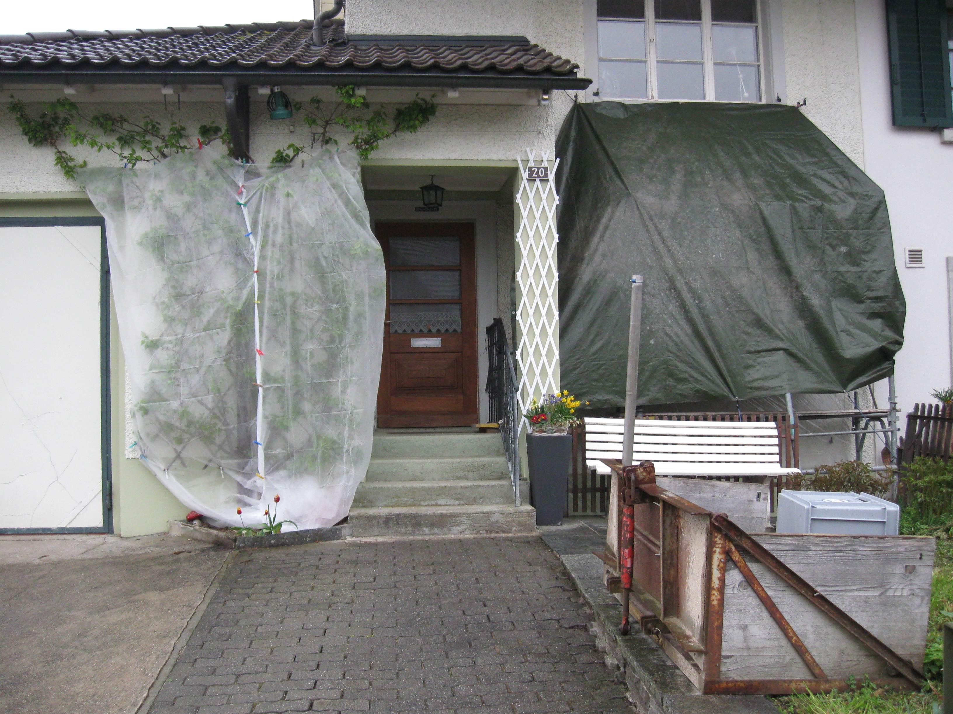 Vor dem Haus wir noch an den Fensterbrüstungen geschliffen und gemalt (hinter grüner Plane)